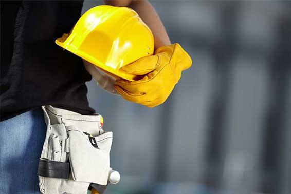 Um homem segurando um capacete de proteção